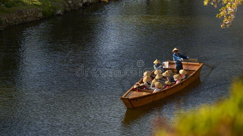 Drewniana łódź na rzece, niesie grupa ludzi jest ubranym ostrostożkowych słomianych kapelusze, Himeji, Japonia zdjęcia royalty free