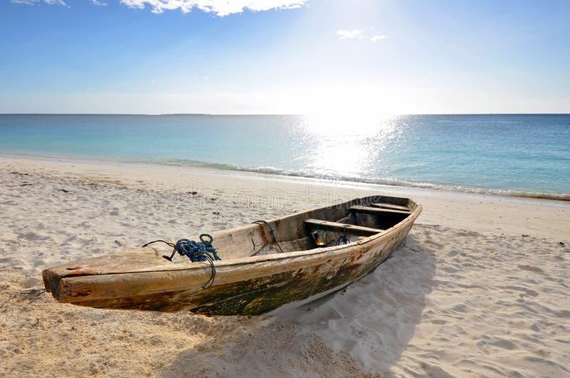 Drewniana łódź rybacka na plaży z niebieskim niebem fotografia stock