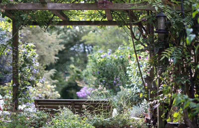 Drewniana ławka pod drewnianym baldachimem z widokiem na well utrzymującym, dobrze zaopatrujący ustronny ogród zdjęcie stock