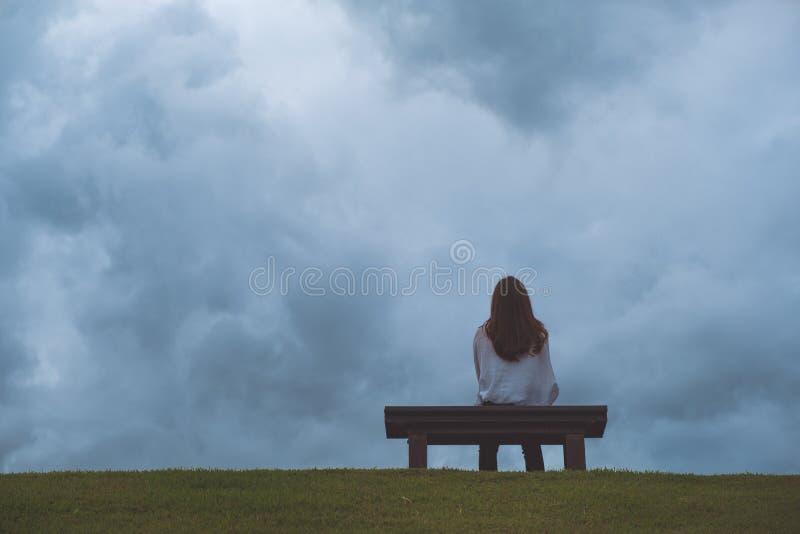 Drewniana ławka w parku z chmurnym i ponurym nieba tłem zdjęcia royalty free
