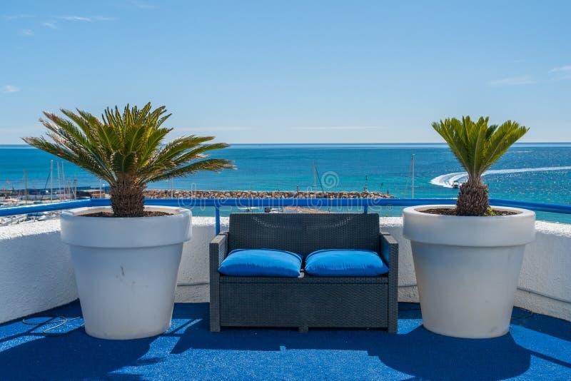 Drewniana ławka z dwa drzewkami palmowymi nad morzem śródziemnomorskim z jasną błękitne wody zdjęcie stock