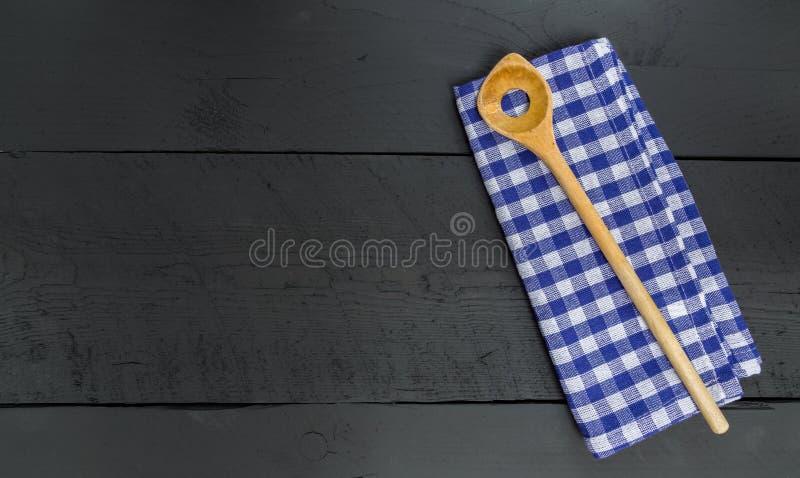 Drewniana łyżka i naczynia płótno na czarnym drewnianym tle zdjęcie stock