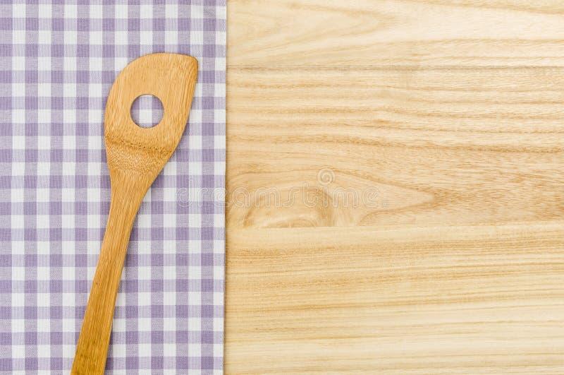 Drewniana łyżka na purpurowym w kratkę stołowym płótnie na drewnianym tle obraz stock
