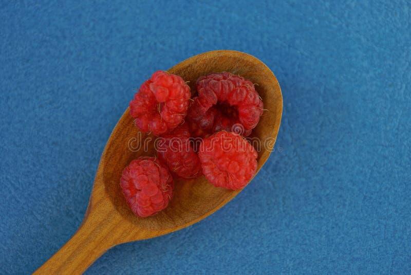 drewniana łyżka z czerwonej malinki jagodami na błękitnym stole obraz royalty free