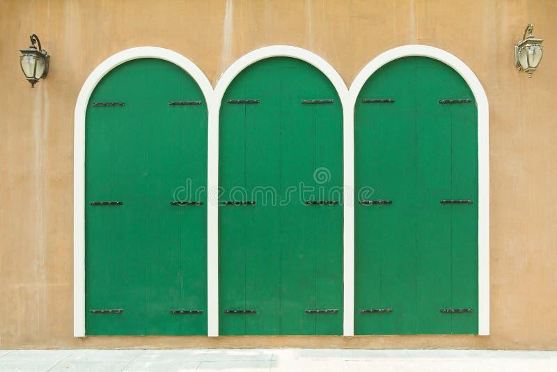 Drewniana ściana i obraz z trzy drzwi zielonym wzorem fotografia royalty free