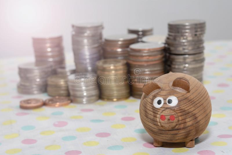 Drewniana świnia z stosem monet, koncepcje oszczędzania pieniędzy, koncepcje inwestycyjne zdjęcia royalty free