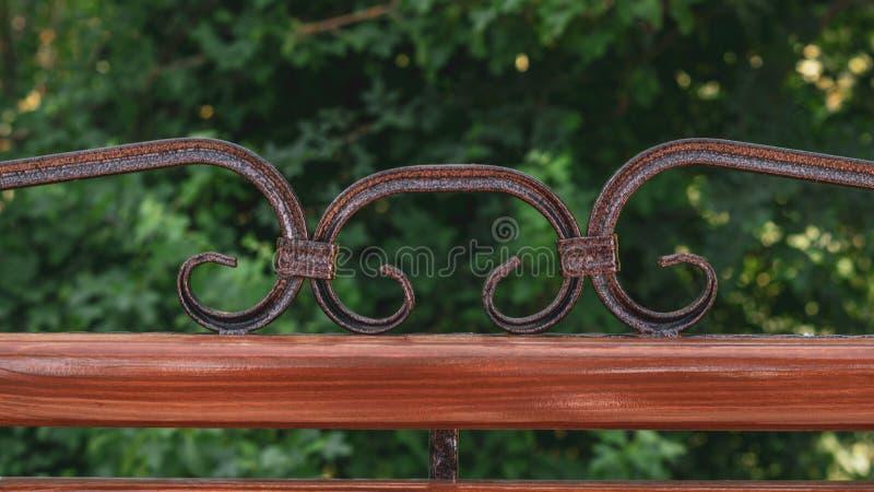 Drewniana ?awka z metal sztuki skuciem w parku rozrywkim Brown ?awka na zielonym tle natura fotografia stock