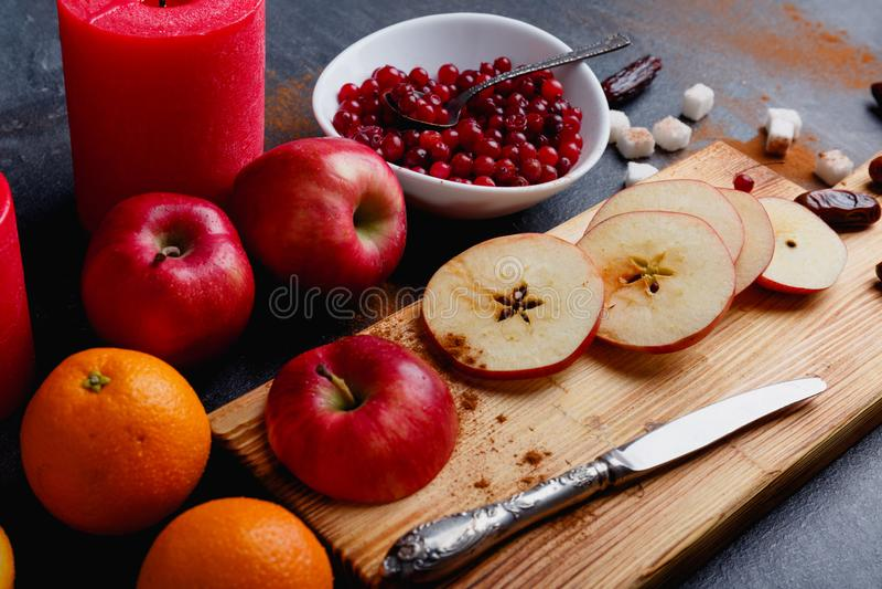 Drewniana deska z pokrojonymi jabłkami, głębokim talerzem z cranberries, pomarańcze i kilka świeczkami, Boczny widok fotografia stock