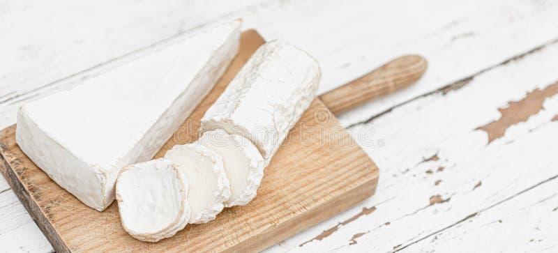 Drewniana deska z różnorodnym serem na białym tle Serowy p??misek kosmos kopii fotografia royalty free