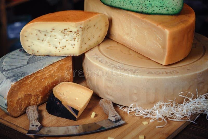 Drewniana deska z różnorodnymi rodzajami smakowity na stole z nożami zielenieje serowego bunkieru ser fotografia royalty free