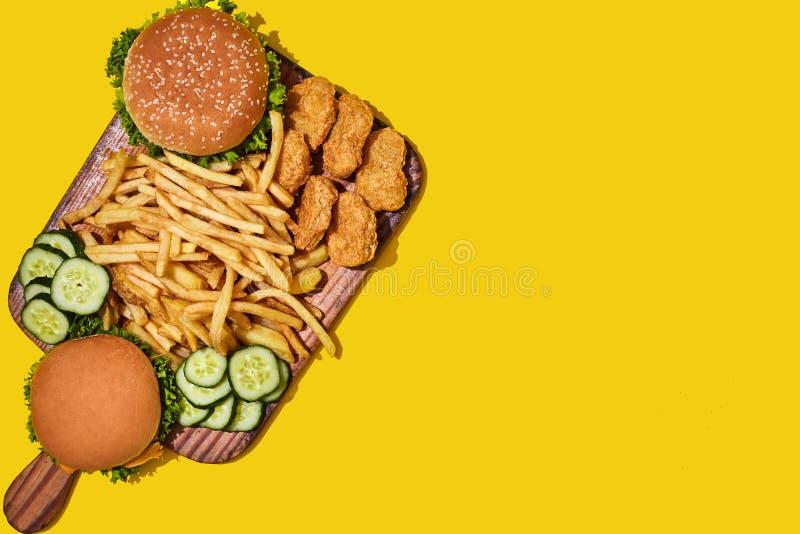 Drewniana deska z różnym fastem food: hamburgery, kurczak bryłki, francuz smażą na żółtym tle obrazy royalty free
