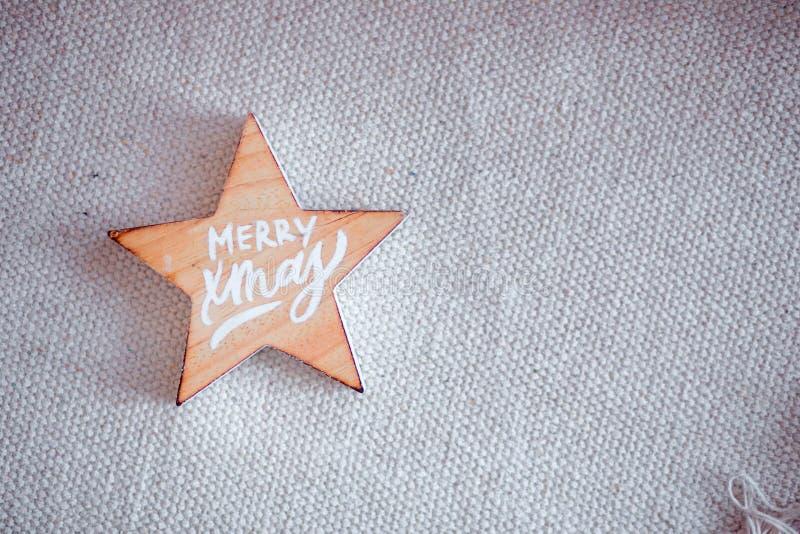 Drewniana gwiazda z wpisowymi szczęśliwych świąt bożego narodzenia kłama na tkaninie obrazy royalty free