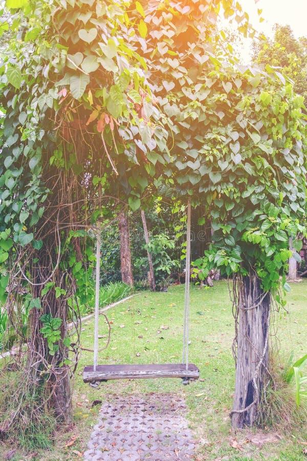 Drewniana huśtawka w ogrodowym roczniku obraz stock