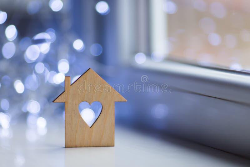 Drewniana ikona dom z dziurą w postaci kierowego pobliskiego okno w świetle dziennym z bokeh zaświeca na zamazanym tle obrazy stock