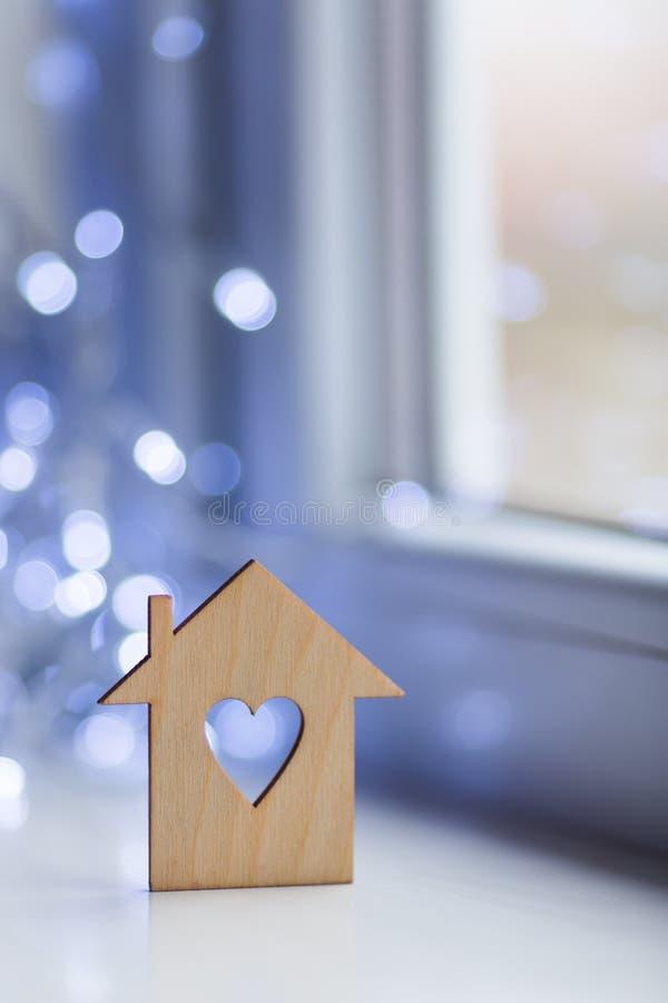 Drewniana ikona dom z dziurą w postaci kierowego pobliskiego okno w świetle dziennym z bokeh zaświeca na zamazanym tle fotografia royalty free