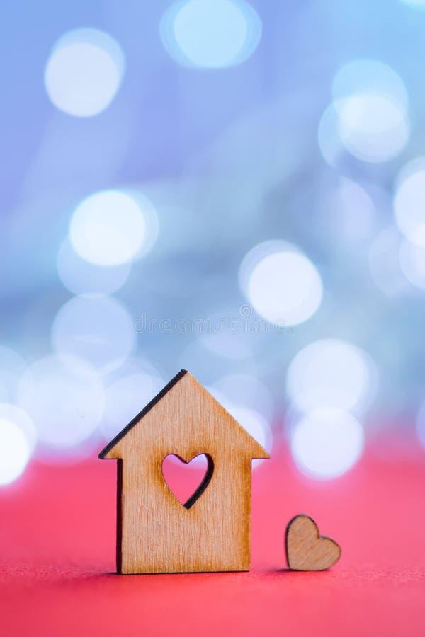 Drewniana ikona dom z dziurą w postaci serca z małym sercem na czerwień stole z lekkim bokeh tłem obrazy stock