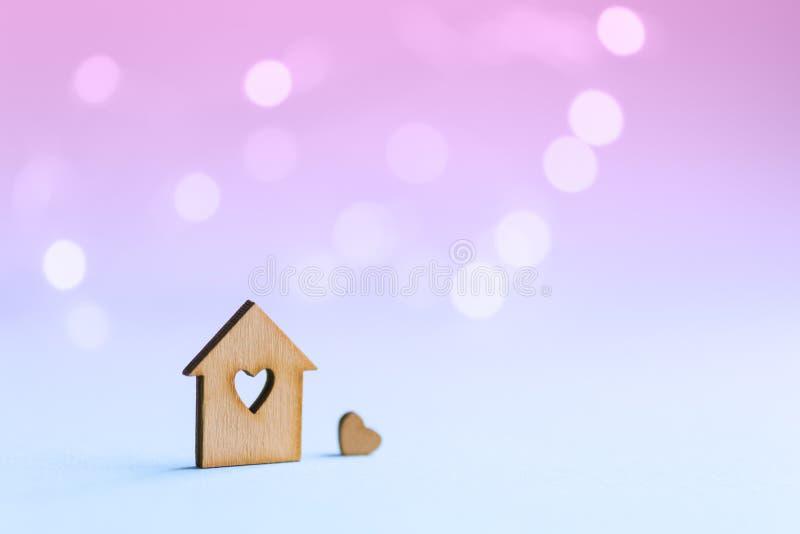 Drewniana ikona dom z dziurą w postaci serca z małym sercem na pastelowym zamazanym tle z lekkim bokeh zdjęcia royalty free