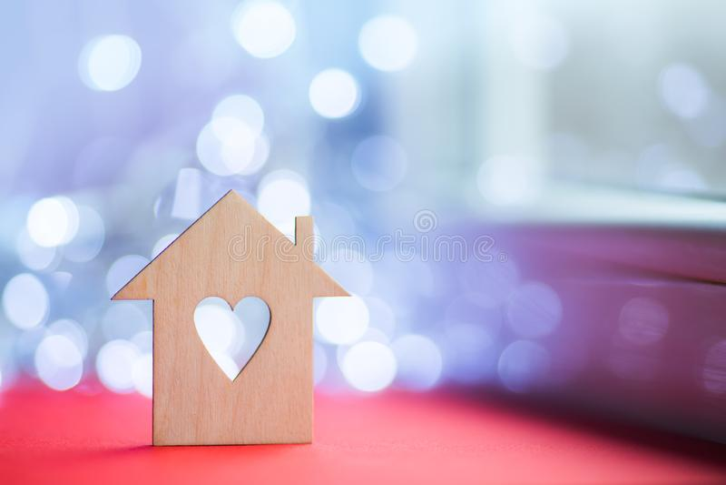 Drewniana ikona dom z dziurą w postaci serca na czerwień stole blisko okno w świetle dziennym z bokeh zaświeca na zamazanym tle zdjęcia royalty free