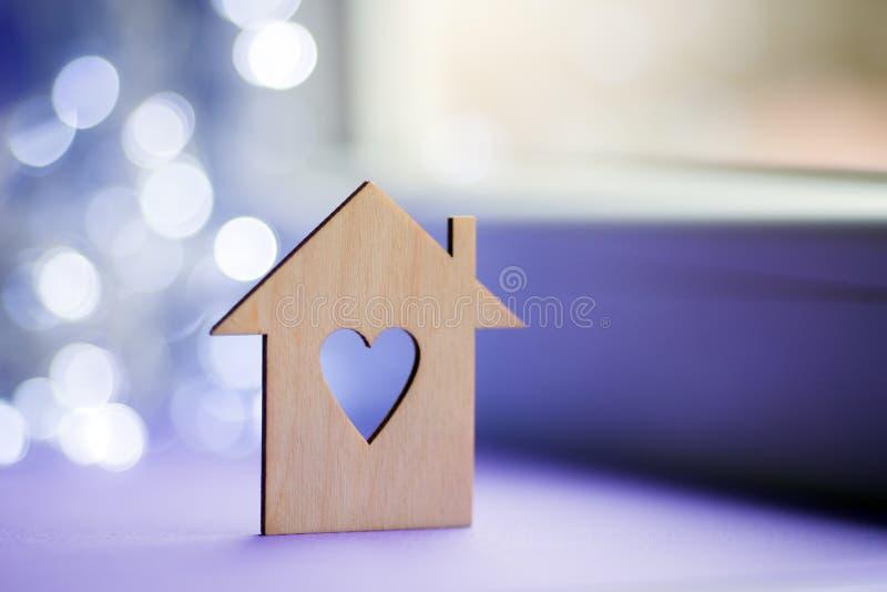 Drewniana ikona dom z dziurą w postaci serca na pobliskim okno w świetle dziennym z bokeh zaświeca na zamazanym purpurowym tle fotografia stock