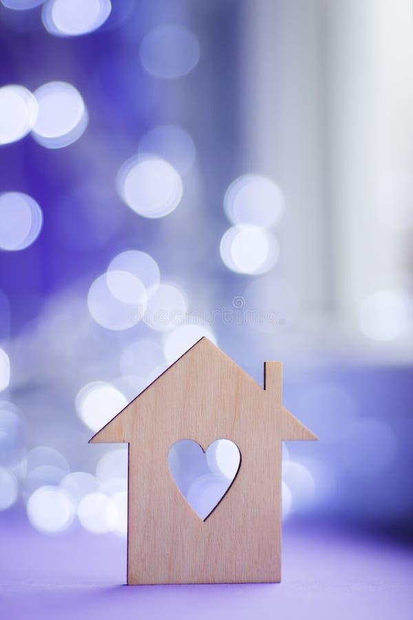 Drewniana ikona dom z dziurą w postaci serca na pobliskim okno w świetle dziennym z bokeh zaświeca na zamazanym purpurowym tle zdjęcia royalty free