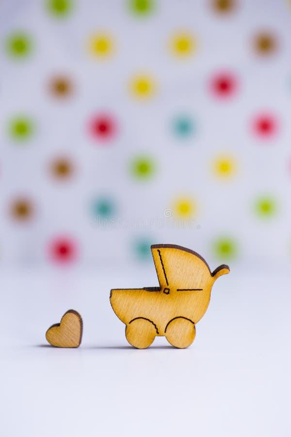 Drewniana ikona dziecko powozik i mały serce na łaciastym tle obrazy royalty free