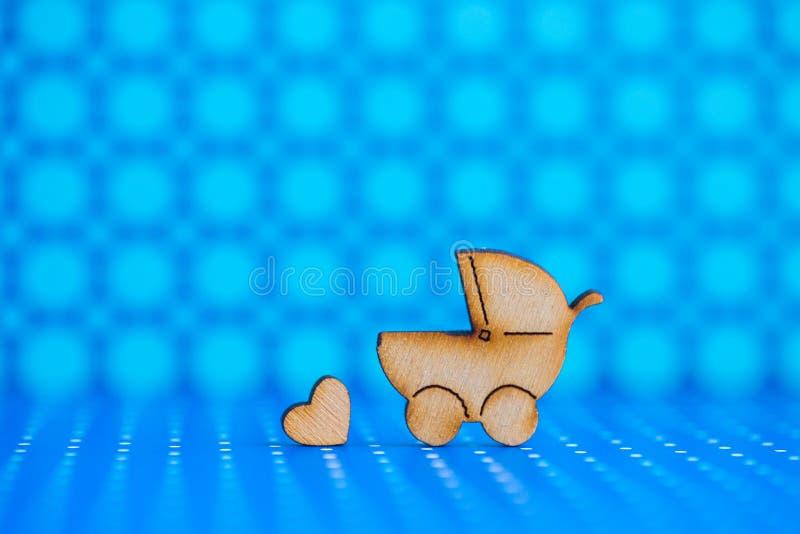 Drewniana ikona dziecko powozik i mały serce na błękitnym łaciastym backg zdjęcia royalty free