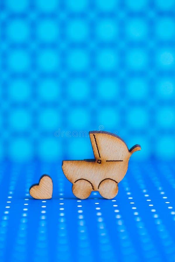 Drewniana ikona dziecko powozik i mały serce na błękitnym łaciastym backg zdjęcia stock