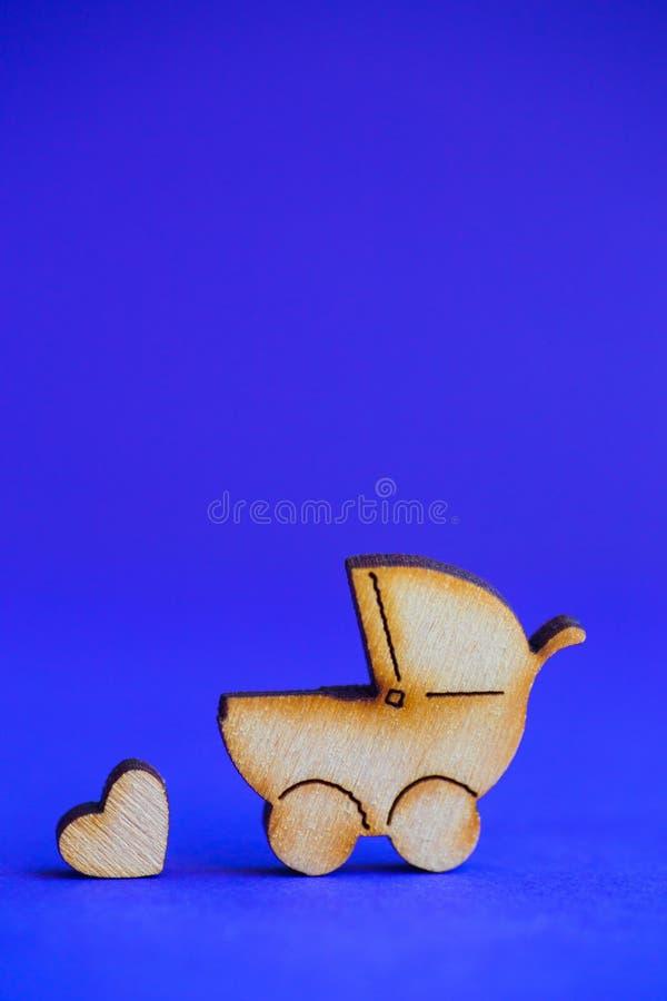 Drewniana ikona dziecko powozik i mały serce na błękitnym tle zdjęcia stock