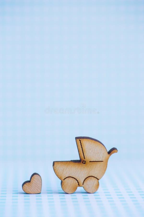 Drewniana ikona dziecko powozik i mały serce na błękitnym w kratkę bac obrazy royalty free