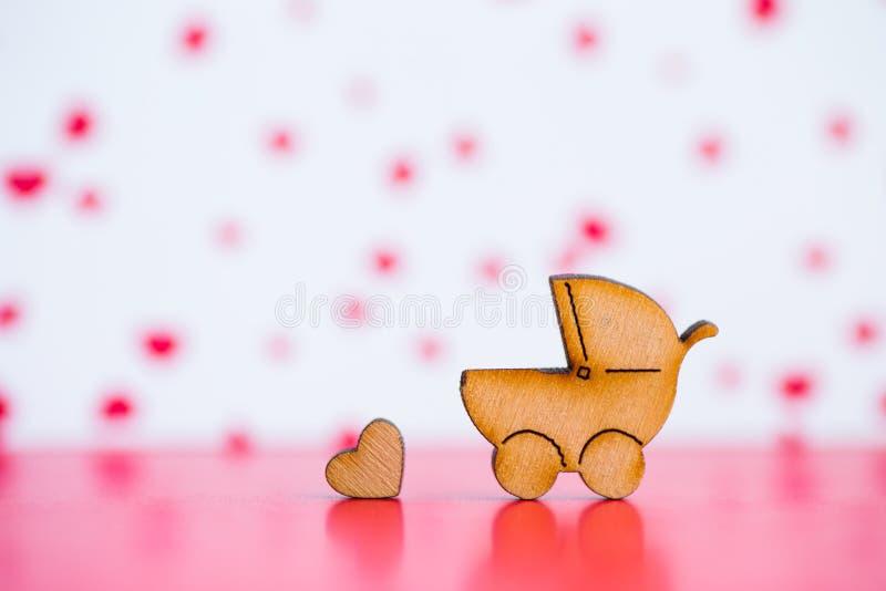 Drewniana ikona dziecko powozik i mały serce na bac różowym i białym fotografia stock