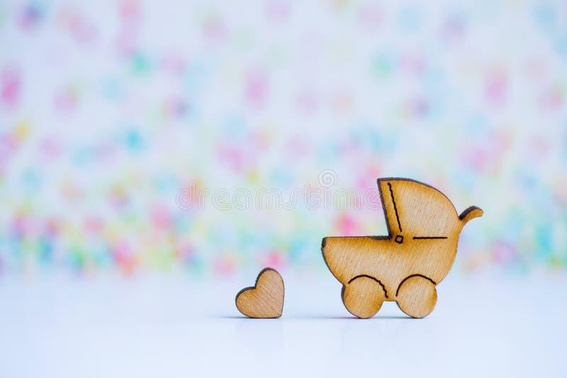 Drewniana ikona dziecko powozik i mały serce na kolorowym backgroun fotografia stock