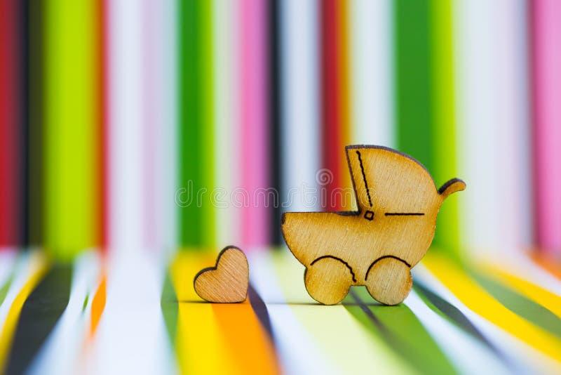 Drewniana ikona dziecko powozik i mały serce na kolorowym pasiastym b zdjęcia royalty free