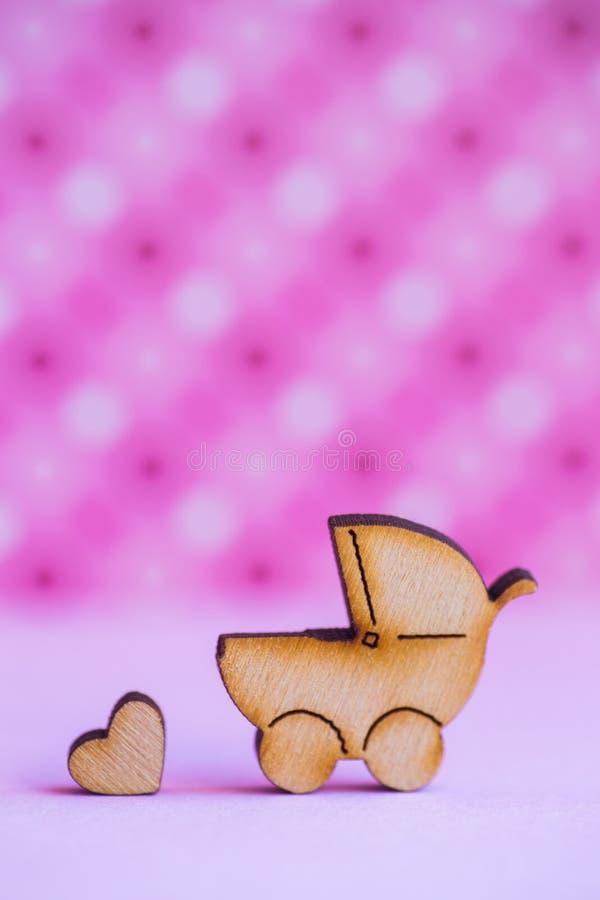 Drewniana ikona dziecko powozik i mały serce na menchiach dostrzegał backg fotografia stock