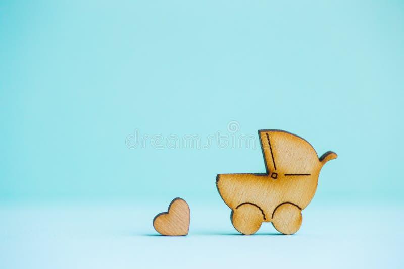 Drewniana ikona dziecko powozik i mały serce na nowym tle zdjęcie royalty free