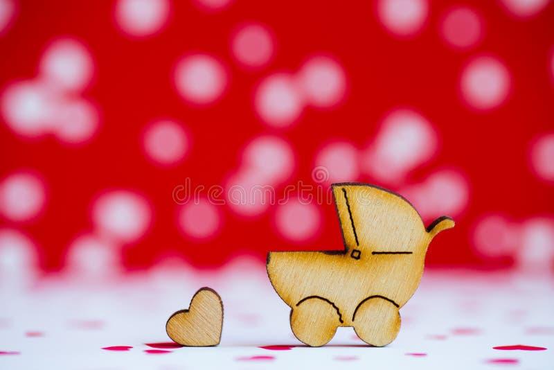 Drewniana ikona dziecko powozik i mały serce na plecy czerwonym i białym zdjęcie royalty free
