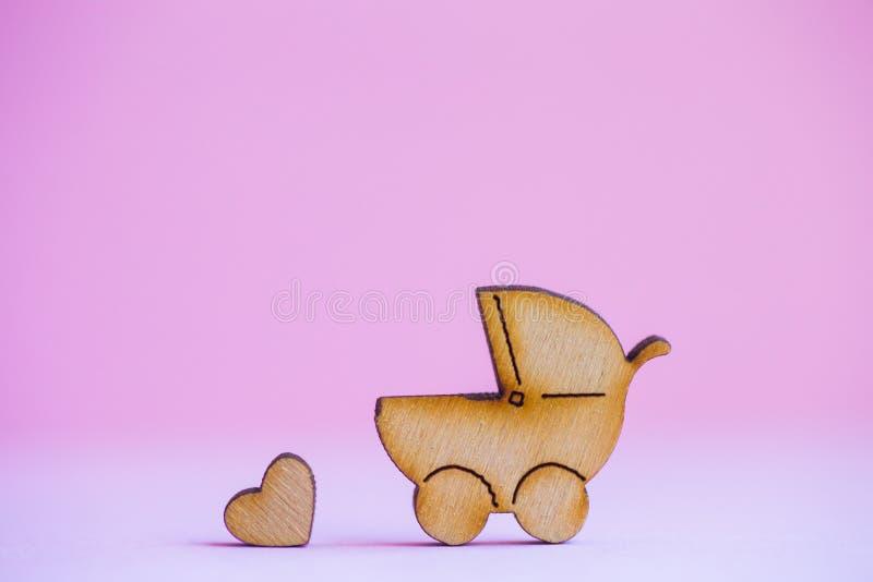Drewniana ikona dziecko powozik i mały serce na różowym tle obrazy stock