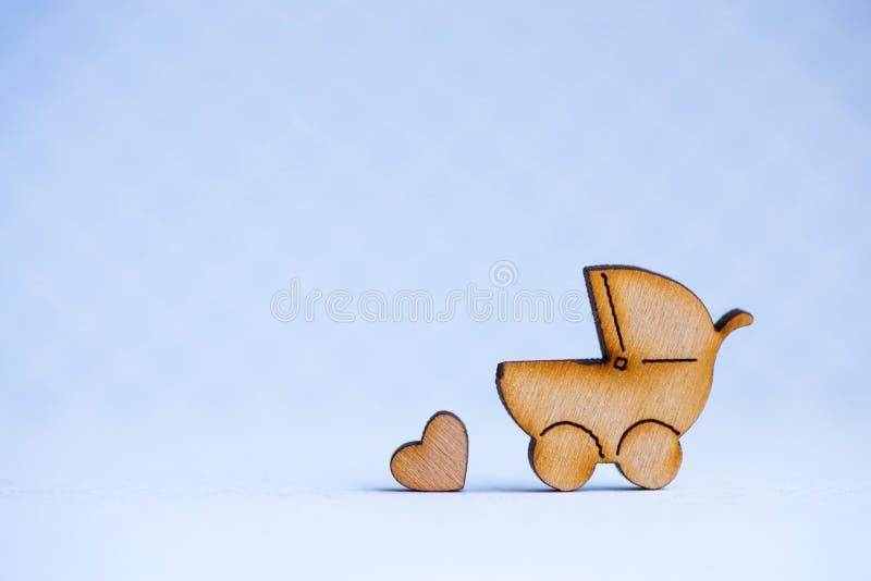 Drewniana ikona dziecko powozik i mały serce na szarym tle zdjęcie royalty free