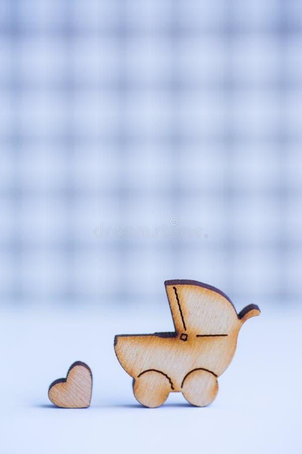Drewniana ikona dziecko powozik i mały serce na w kratkę backgrou obraz stock