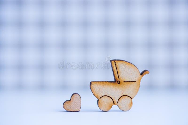 Drewniana ikona dziecko powozik i mały serce na w kratkę backgrou fotografia stock