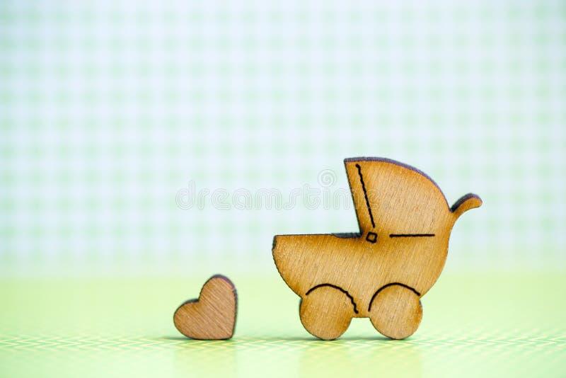 Drewniana ikona dziecko powozik i mały serce na zielonych w kratkę półdupkach obrazy royalty free