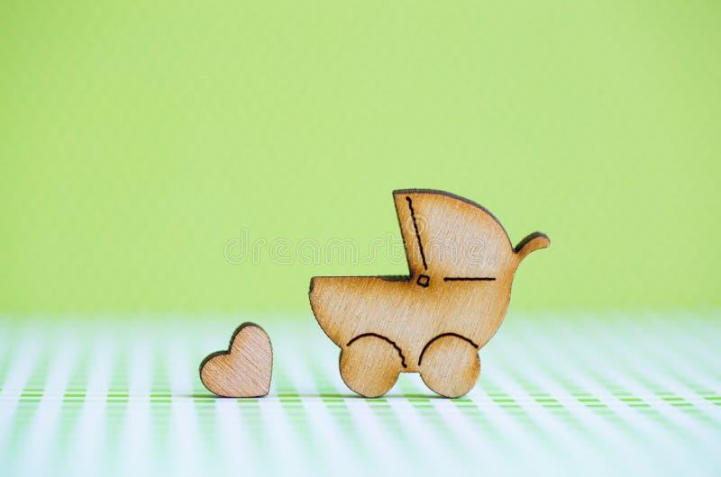 Drewniana ikona dziecko powozik i mały serce na zielonym tle obraz royalty free
