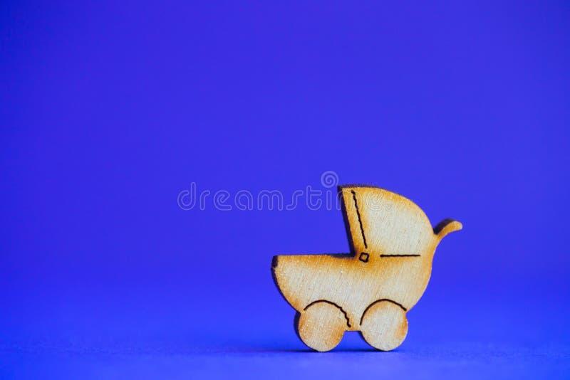 Drewniana ikona dziecko powozik na błękitnym tle zdjęcia stock