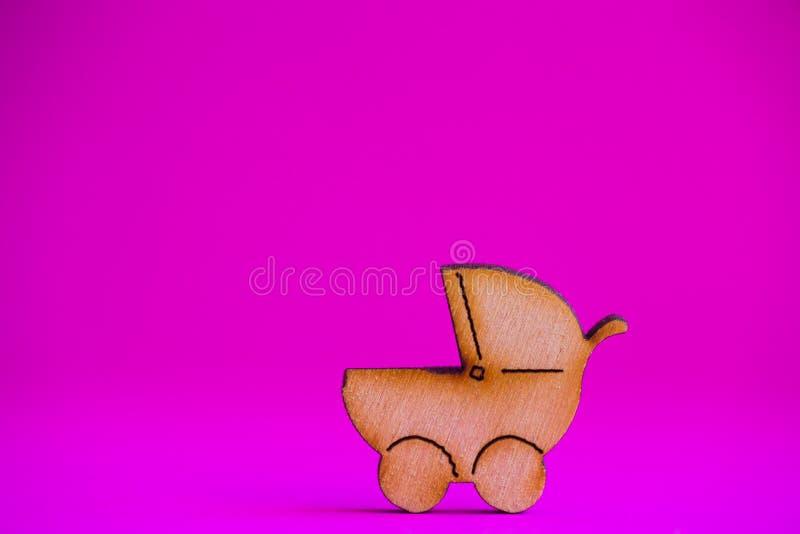 Drewniana ikona dziecko powozik na ciemnopąsowym tle obraz royalty free