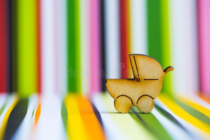 Drewniana ikona dziecko powozik na kolorowym pasiastym tle zdjęcie stock