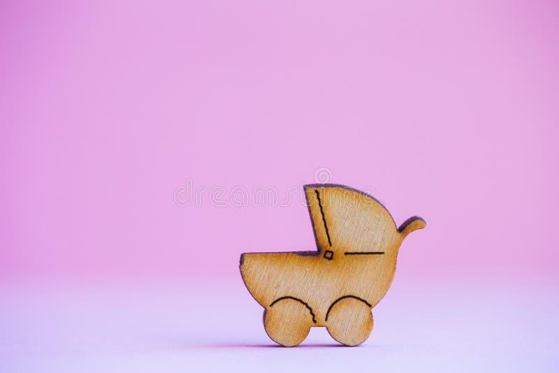Drewniana ikona dziecko powozik na różowym tle obrazy royalty free