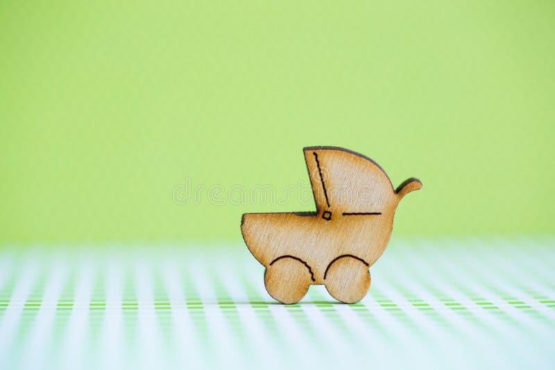 Drewniana ikona dziecko powozik na zielonym tle fotografia royalty free
