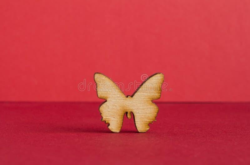 Drewniana ikona motyl na czerwonym tle obraz stock