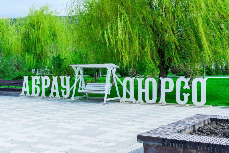 Drewniana inskrypcja Abrau-Durso biały kolor i przestronna huśtawka między słowami przeciw tłu zieleń obraz stock