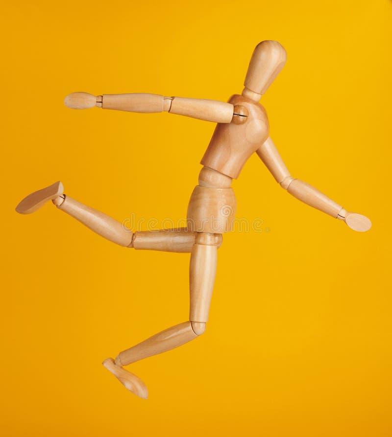 Drewniana lala w kopnięcie balowej pozie fotografia royalty free
