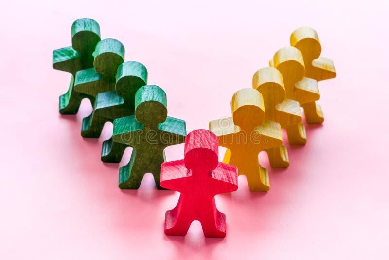 Drewniana ludzka czerwona figura wyróżnia się od tłumu na różowym biurku Przywództwo, koncepcja zarządzania zdjęcia royalty free